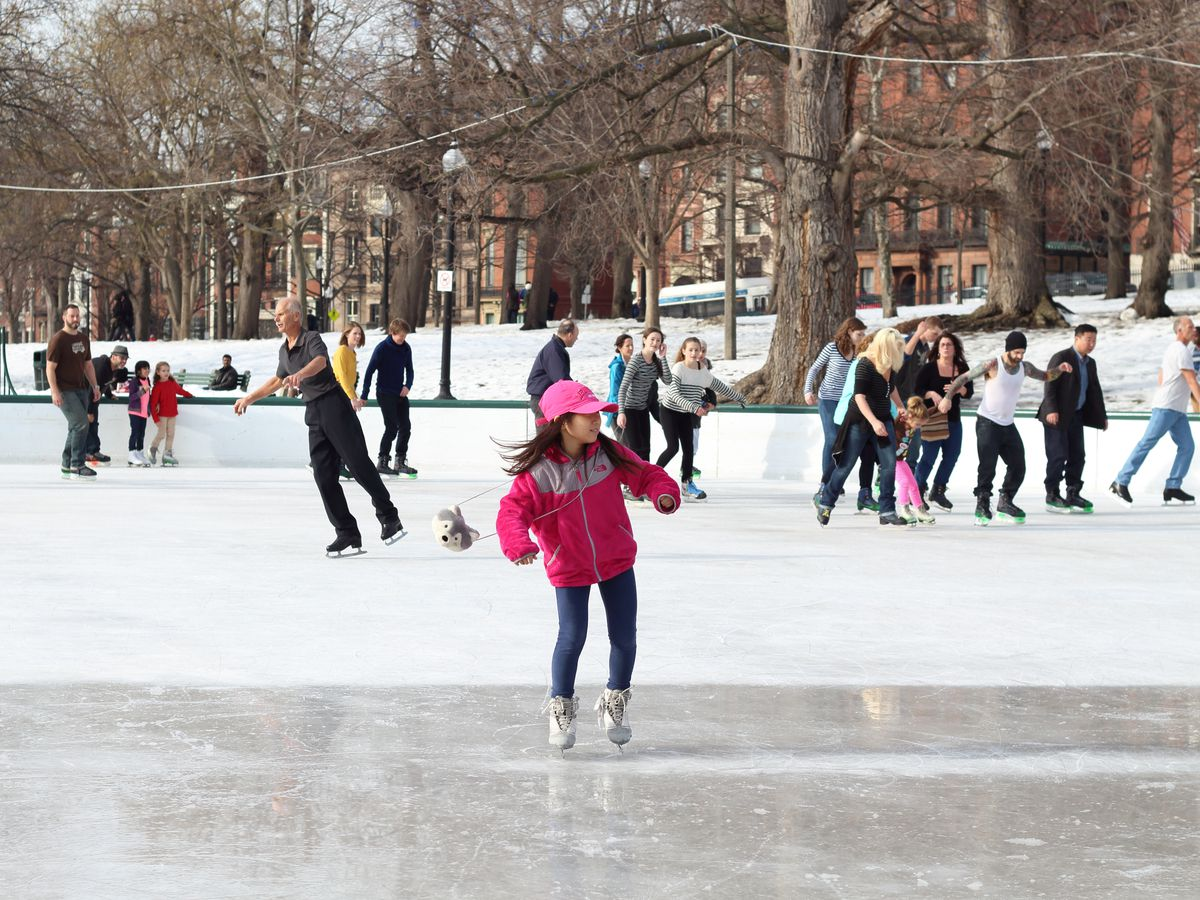 A kid ice-skating on an open-air rink with more people in the background.