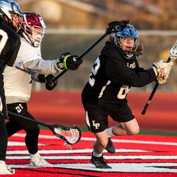 Lone Peak's Josh Bentley moves the ball behind American Fork's goal in a boys lacrosse game in American Fork on Tuesday, March 30, 2021.