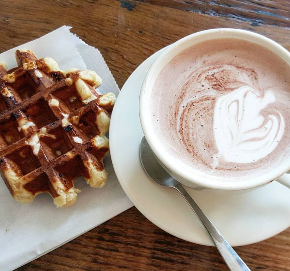 A Liege-style waffle sits next to a frothy hot chocolate in a white cup and saucer