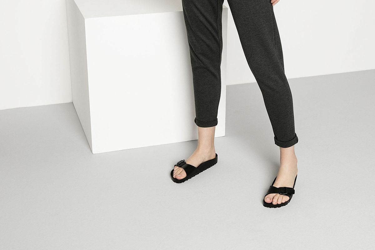 A model wearing black Birkenstock sandals, gray pants, and a gray tee shirt