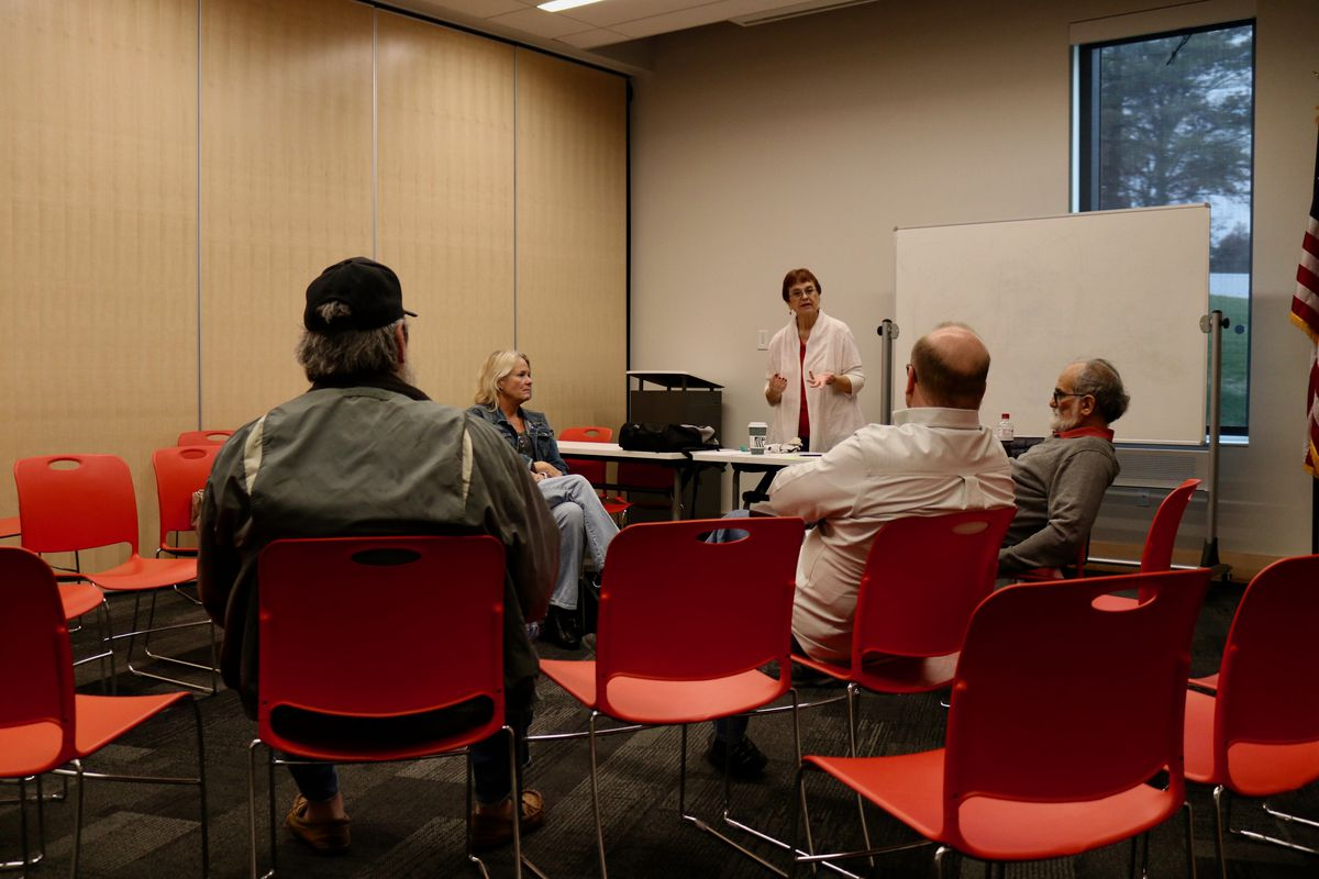 A woman stands beside a whiteboard in a conference room and speaks to a group of five people seated on chairs.