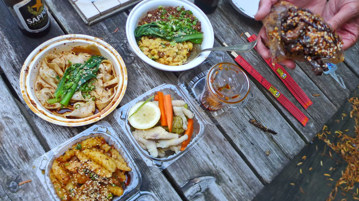 A wooden table outdoors seen from above with Chinese food spread across it.