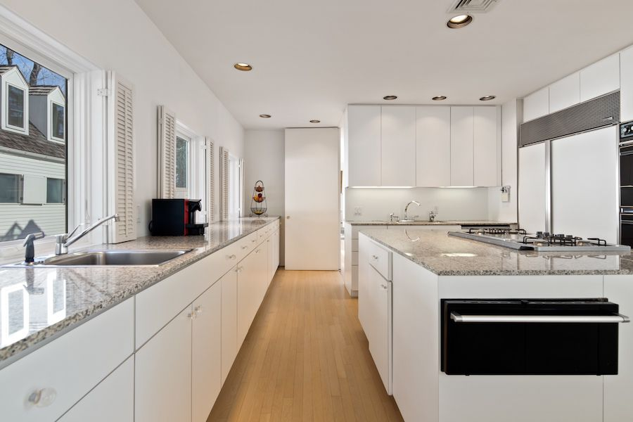 A kitchen with white cabinets, gray countertops, and wood floors.