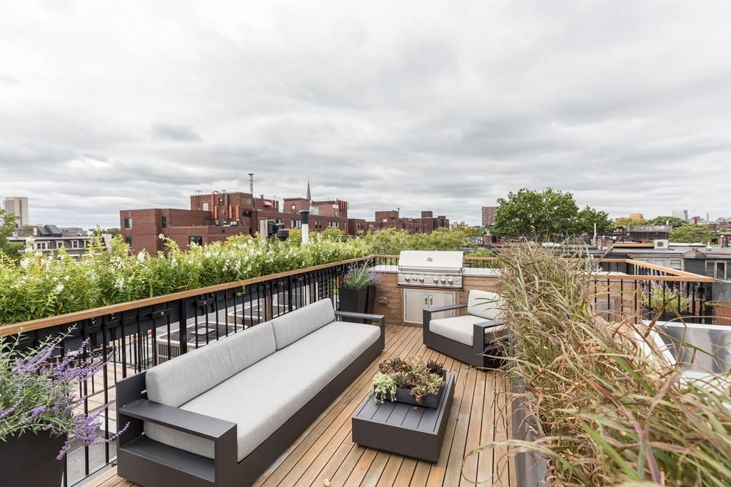A roof-top deck with furniture and a grill.