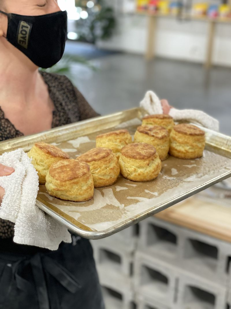 woman holding tray with biscuits