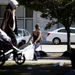 A woman drags her belongings away as Salt Lake City police officers and Salt Lake County Health Department employees clean up 500 West in Salt Lake City on Wednesday, Sept. 28, 2016.