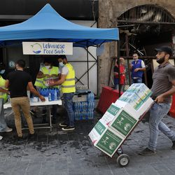A man carries donated food as he passes in front of a tent that citizens set up to offer people food and drinks, on a street that was damaged by last week's explosion, in Beirut, Lebanon, Tuesday, Aug. 11, 2020. In the absence of the state, acts of kindness and solidarity have been numerous and striking. Many extended a helping hand far beyond their circle of friends or family, taking to social media to spread the word that they have a room to host people free of charge.