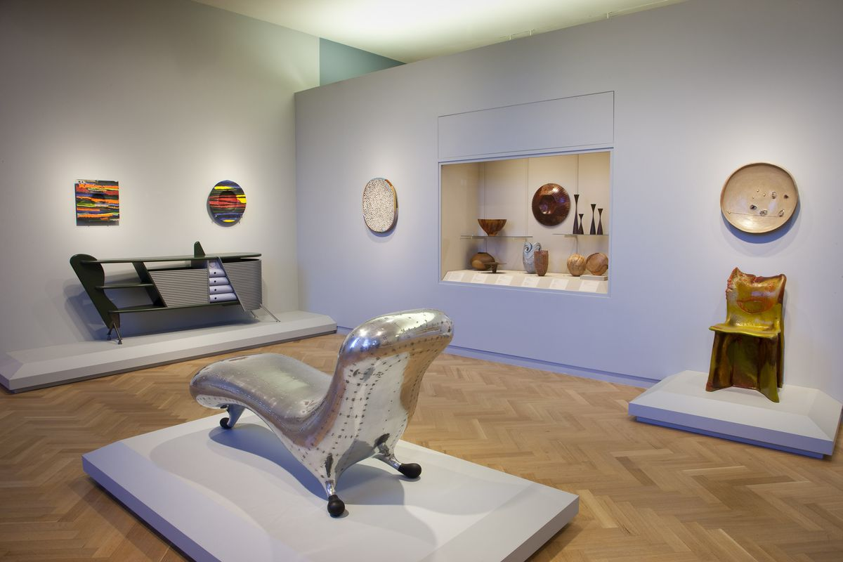 A room in the Carnegie Museum of Art in Pittsburgh. There are items of furniture and design objects positioned around the room on shelves and on stands on the floor.