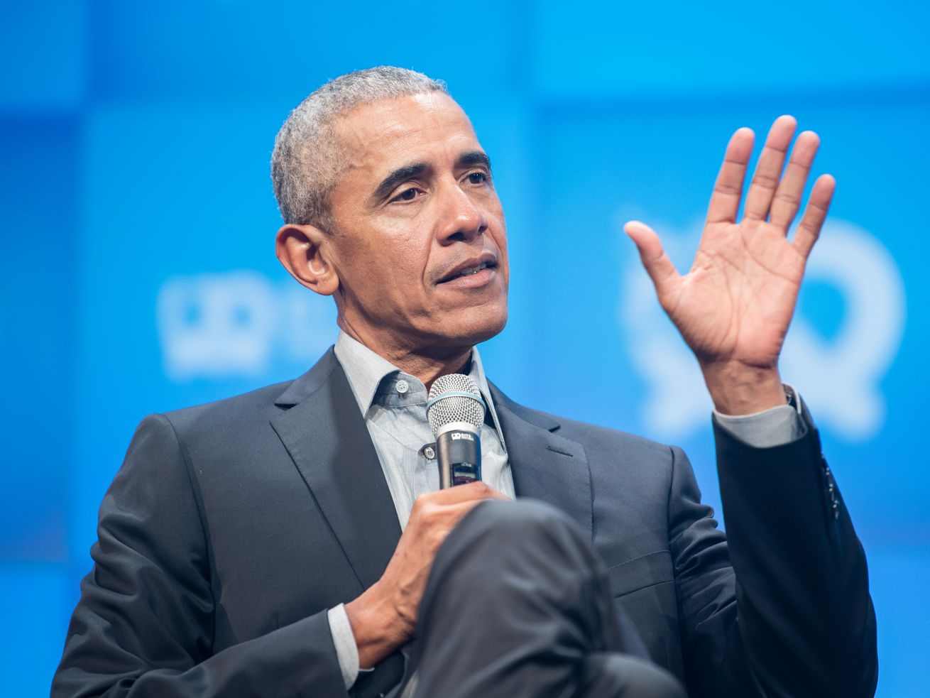 A seated Obama, in a dark suit and gray shirt similar to the one he wore for his 2020 HBCU commencement address, gestures with his left hand as he speaks into a microphone.