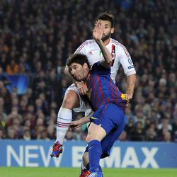FC Barcelona's Lionel Messi from Argentina, front, duels for the ball with AC Milan's Antonio Nocerino during their Champions League second leg, quarterfinal soccer match, at Camp Nou stadium in Barcelona, Spain Tuesday April 3, 2012.  FC Barcelona won 3-1.