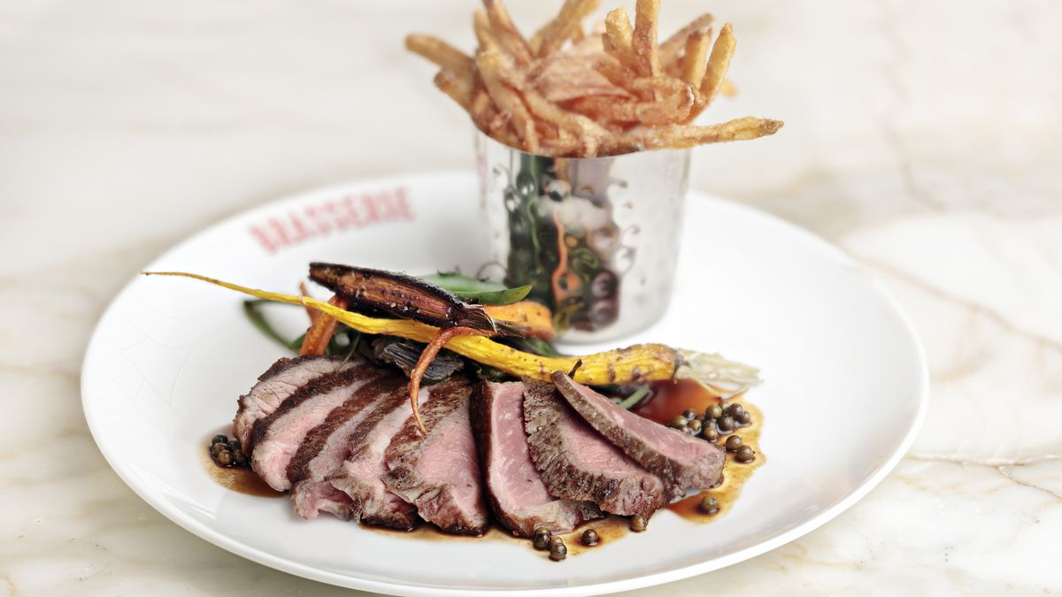 """Thinly sliced rare steak is fanned out on a white plate with a side of fries. The plate says """"brasserie"""" on the rim and sits on a light marble surface."""