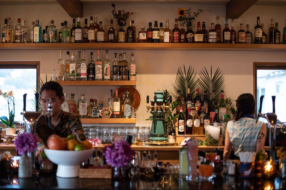 Garnishes and fruits at a bar with bottles in the background.
