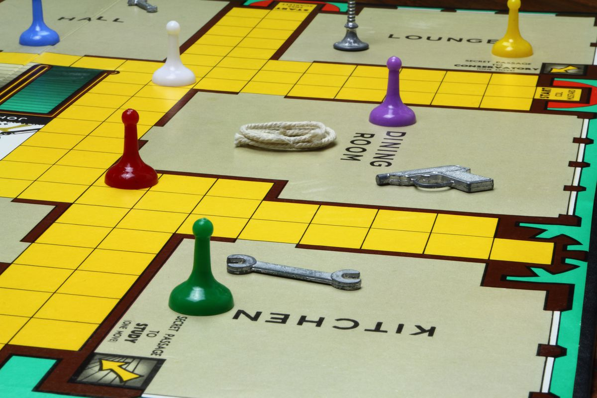 A close-up view of a board game showing colorful pieces on a floor plan of a mansion, with rooms like kitchen and dining room.