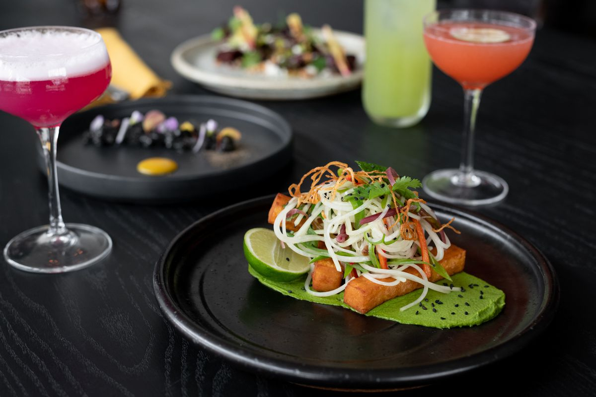 On a dark table are three drinks and three dishes. In the foreground, the first dish is fried masa wedges topped with swirling shred of vegetables and garnished with herbs and black sesame. On the plate is a pool of vibrant green sauce. The drinks are pink, pale orange, and green. The other dishes are a curl of black with edible flowers, and a barely visible collection of beets garnished with