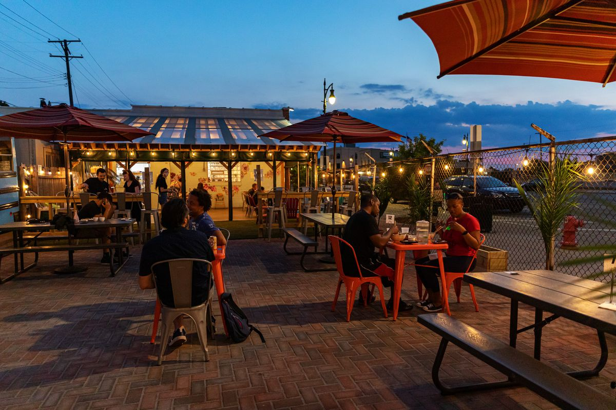 The patio at Ima in Corktown in the evening where customers are seated at physically distant tables.
