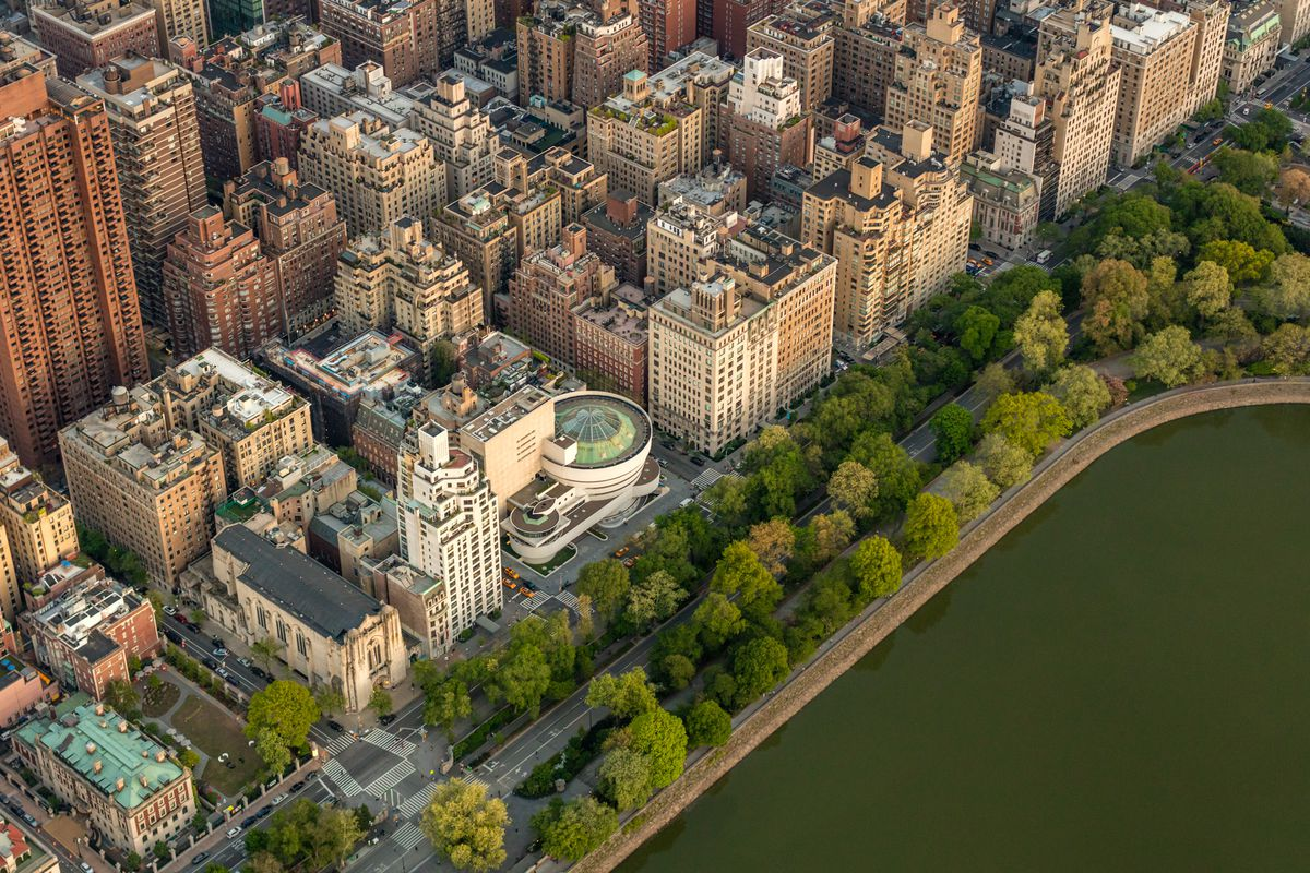 An aerial view of the Upper East Side in New York City, with Central Park's reservoir and green trees on one side, and apartment buildings and the Guggenheim Museum on the other.