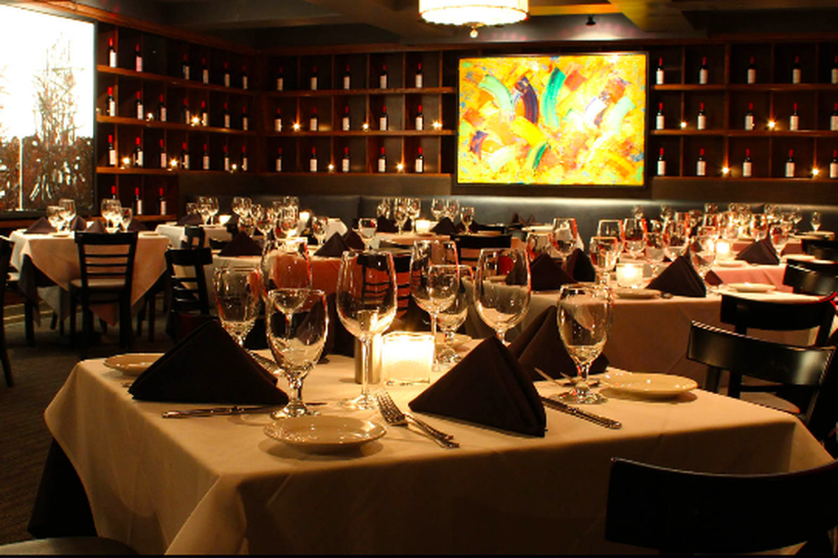 A dimly lit dining room with tables draped in white tablecloths, a striking art fixture, and dark wood cabinets