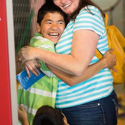 Scott, 14, and Deanne Walker hug at the Museum of Natural Curiosity. Scott, who has cerebral palsy, had just completed the ropes course, and the whole family was proud of him.