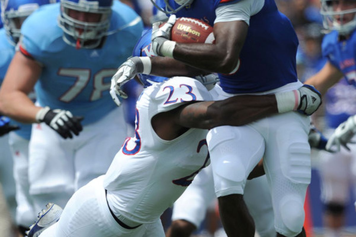 Apr 28, 2012; Lawrence, KS, USA; Kansas Jayhawks running back Tony Pierson (3) is tackled by cornerback Dexter Linton (23) in the first half of the Spring Game at Memorial Stadium. Mandatory Credit: John Rieger-US PRESSWIRE