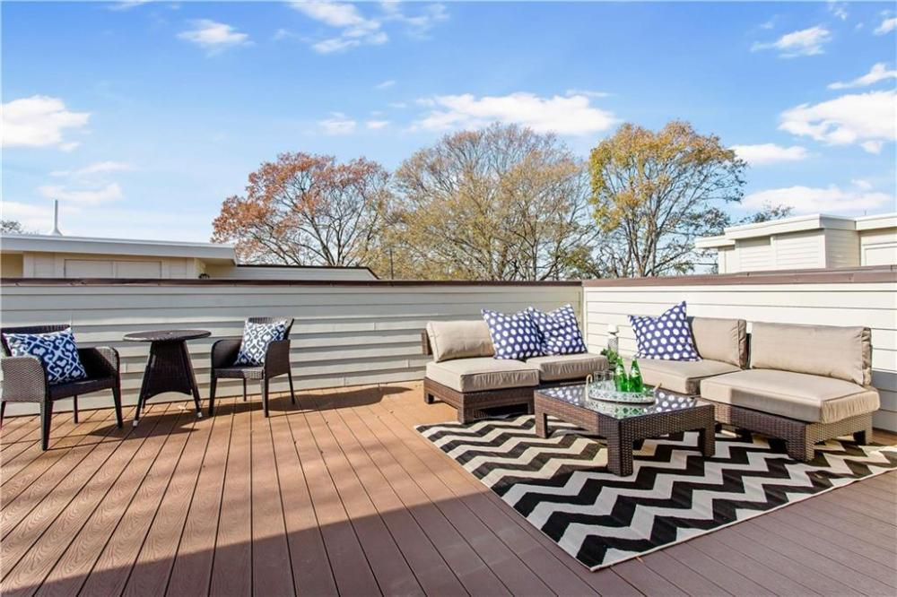 A large roof deck with a bunch of chairs.