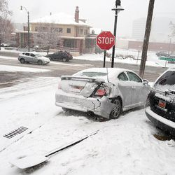 Two cars collided during the treacherous drive in the Avenues following an ice storm in Salt Lake City on Thursday, Dec. 19, 2013. A unicyclist makes his way past the scene.
