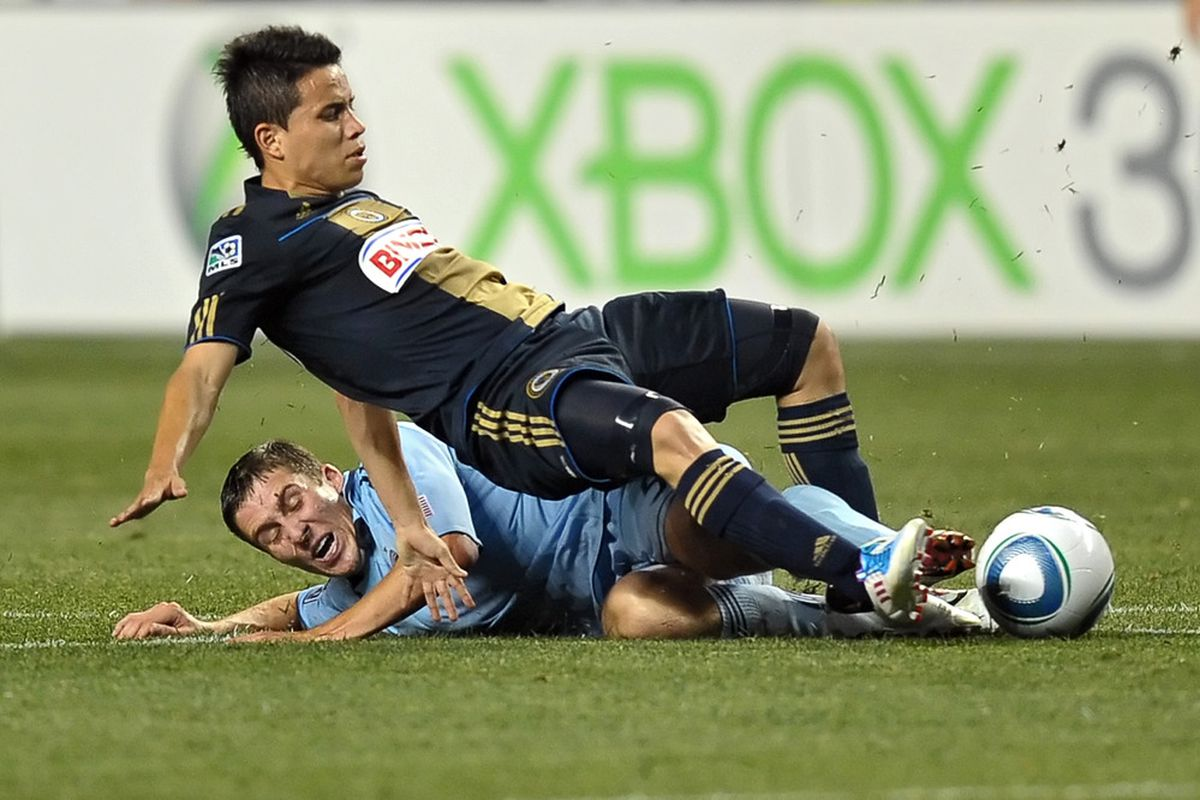 CHESTER, PA - JUNE 22: Roger Torres #8 of the Philadelphia Union is tackled from behind by Matt Besler #5 of Sporting Kansas City at PPL Park on June 22, 2011 in Chester, Pennsylvania. The game ended 0-0. (Photo by Drew Hallowell/Getty Images)