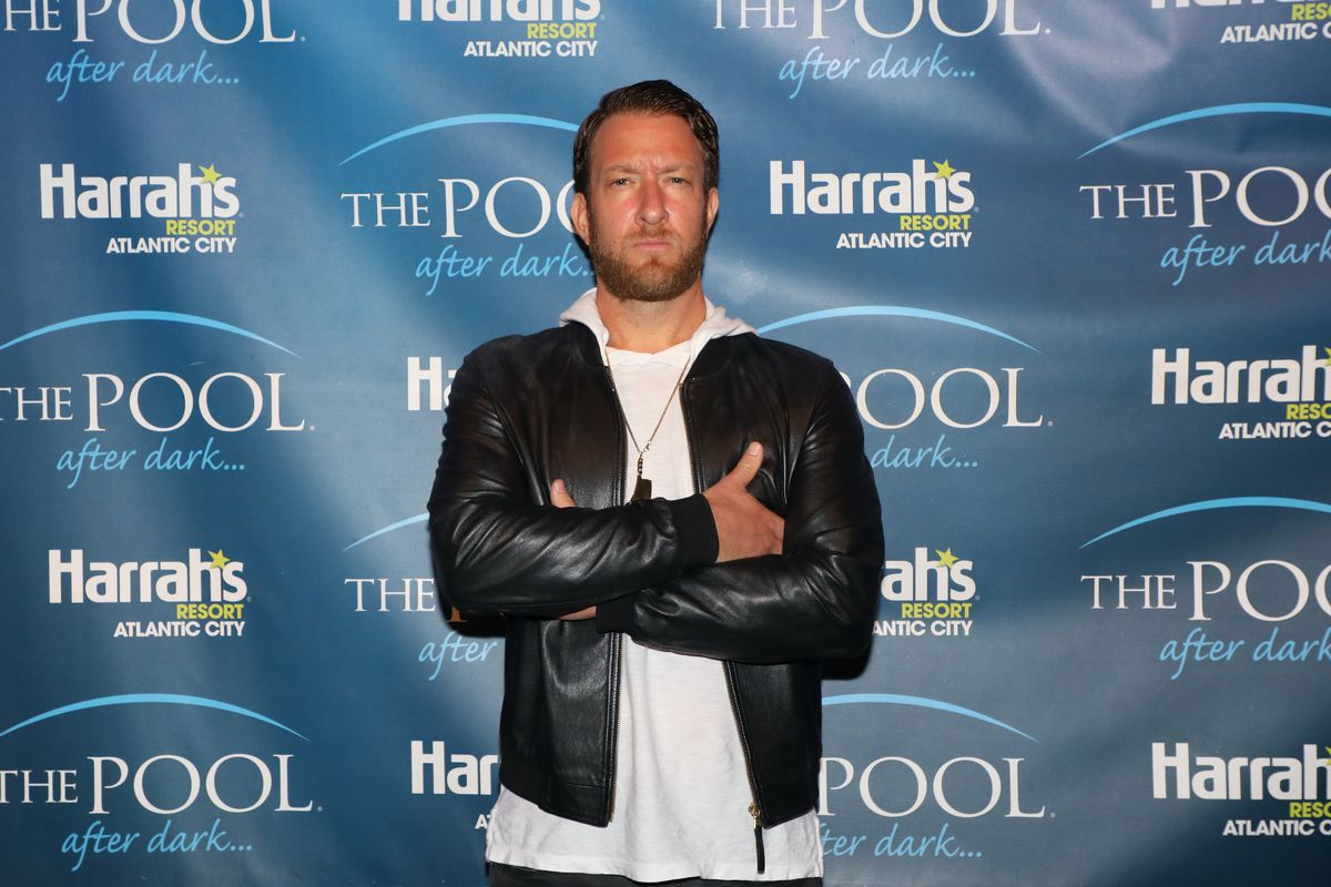 Barstool Sports founder Dave Portnoy standing in front of a photo backdrop at a Harrah's casino event.