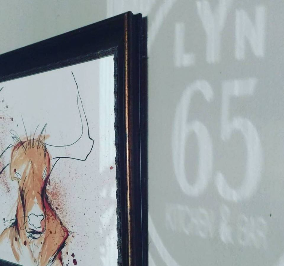 A print of a watercolor cow on a gray wall with the reflection of the Lyn 65 logo shadow
