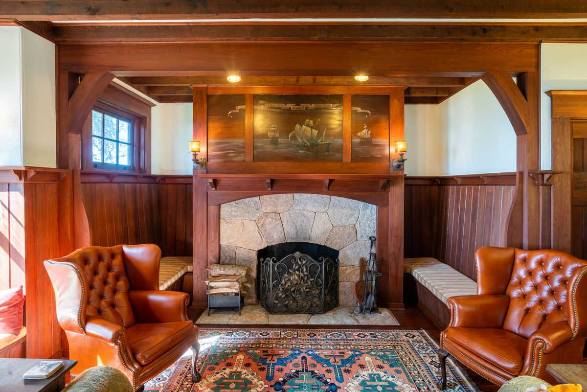 A fireplace has two leather chairs and a rug in front of it.