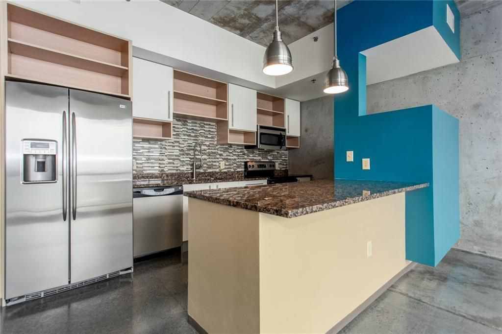 Kitchen with empty shelves, tile backsplash, stainless appliances and blue accent wall.