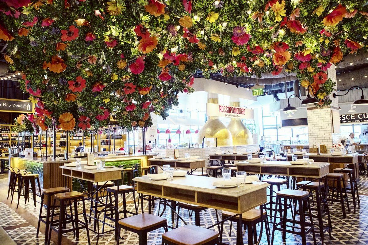 A floral pop-up bar with bar-sized tables and lots of flowers hanging from above.