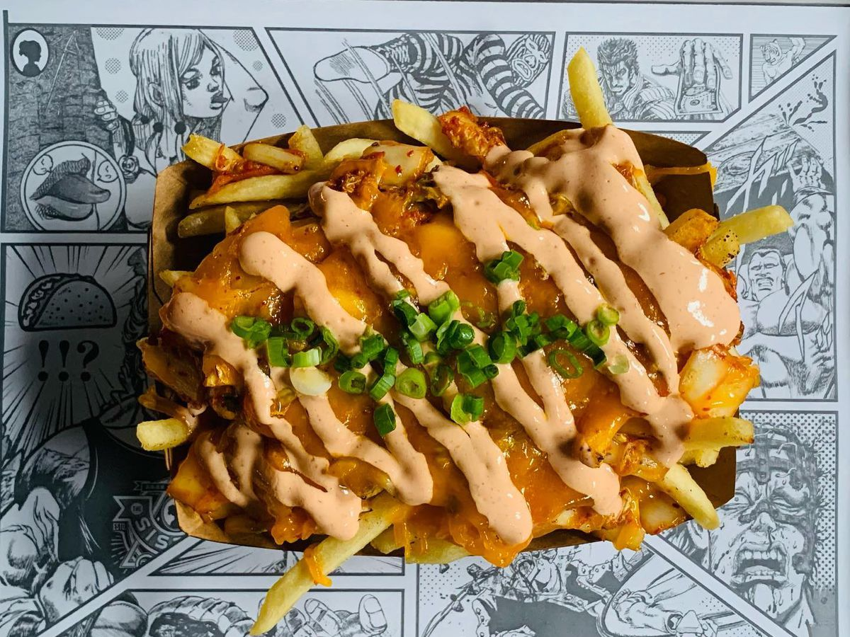 From above, a paper basket of fries covered in sauce and kimchi slices, on a paper placemat depicting comics panels