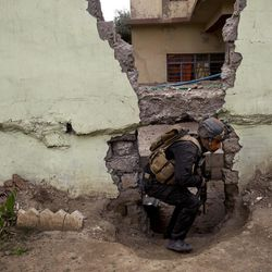 An Iraqi special forces soldier moves through a hole in a wall during heavy fighting in the Yarmouk district of western Mosul, Iraq, Tuesday, April 11, 2017.