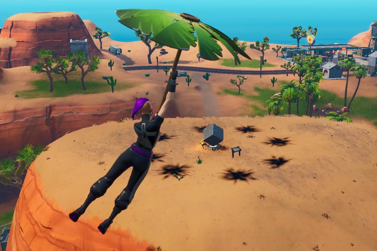 A player gliding in toward the desert Fortnite cube memorial