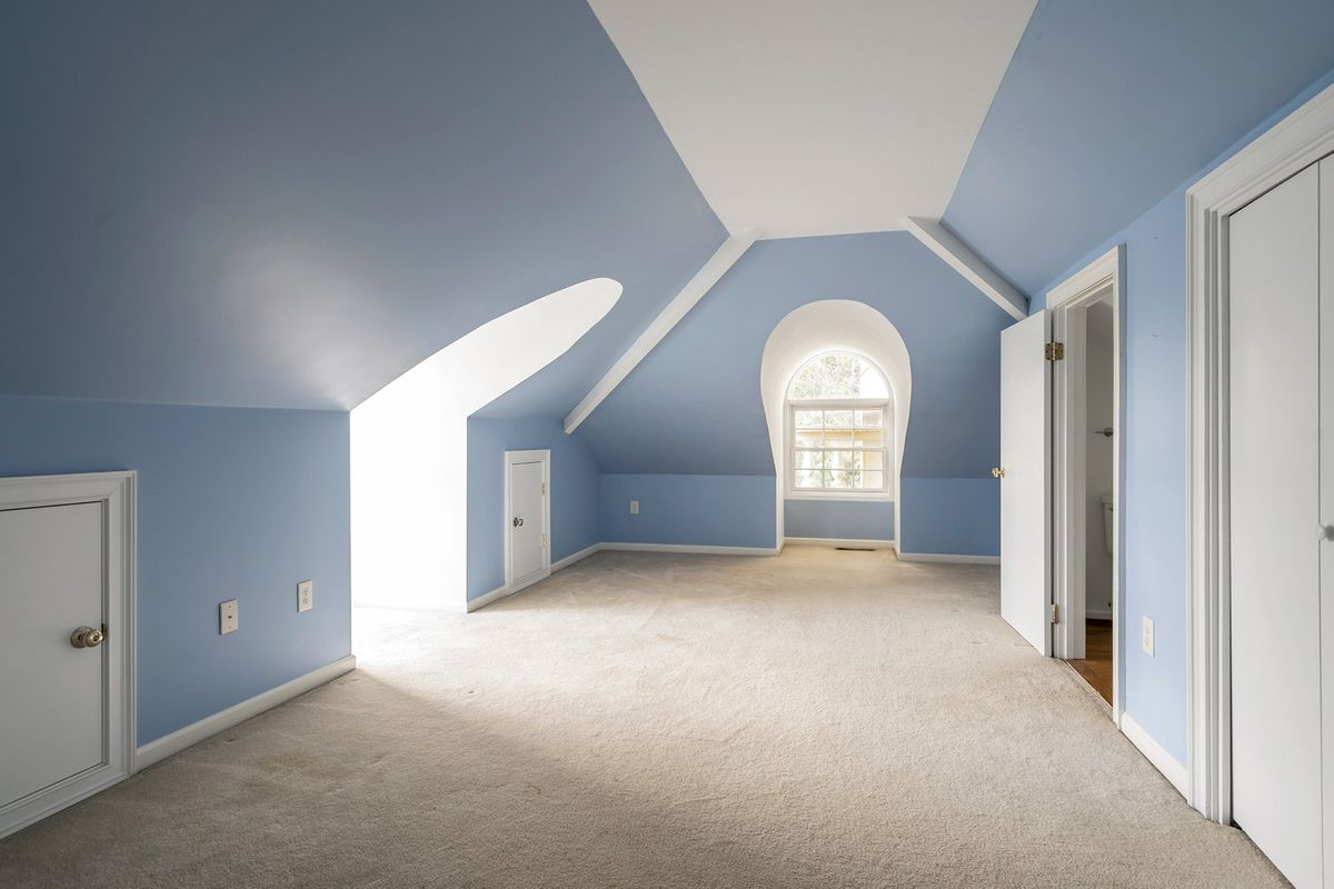 A long blue room in the attic of a classical house.