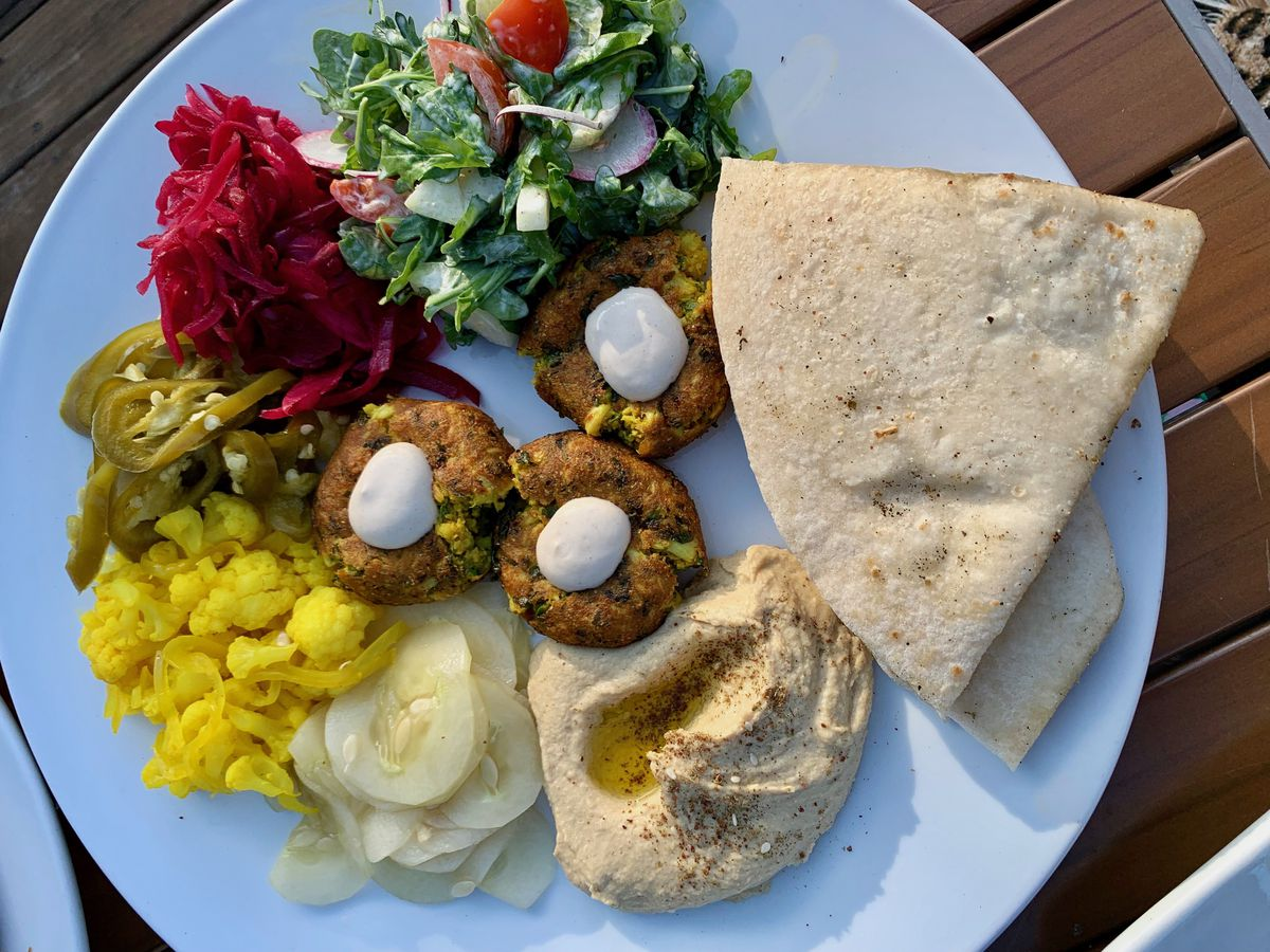 From above, a plate of balls of falafel surrounded by salad, piles of pickled vegetables, a mound of hummus, and triangles of flatbread
