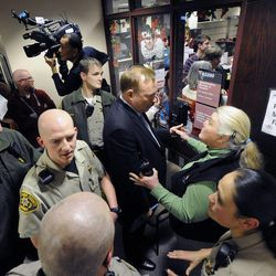 State Sen. Jim Debakis tries to convince Salt Lake County Sheriff's Capt. Kendra Herlin to let those who arrived late to still obtain a marriage license from the county clerk's office after a federal judge ruled that Amendment 3, Utah's same-sex marriage ban, is unconstitutional on Friday, Dec. 20, 2013.