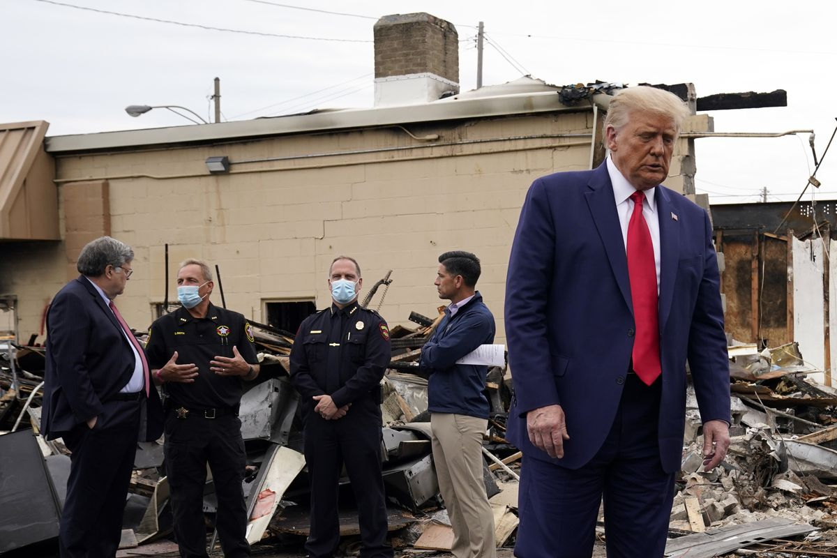 President Donald Trump turns around after talking with law enforcement officials Tuesday as he tours an area damaged during demonstrations in Kenosha, Wis.