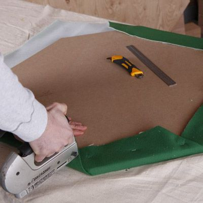Person stapling the felt onto the under side of the table.