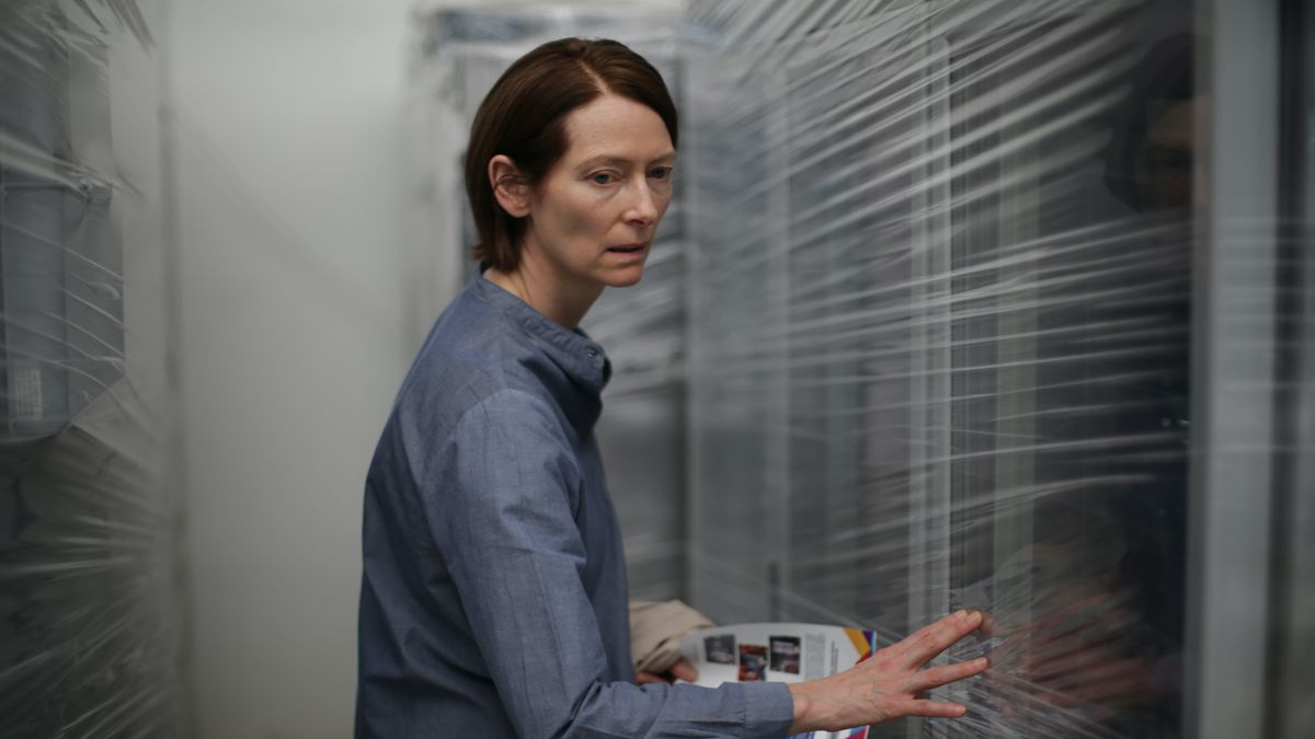 Tilda Swinton looking confused against a blurred background of white slats in Memoria