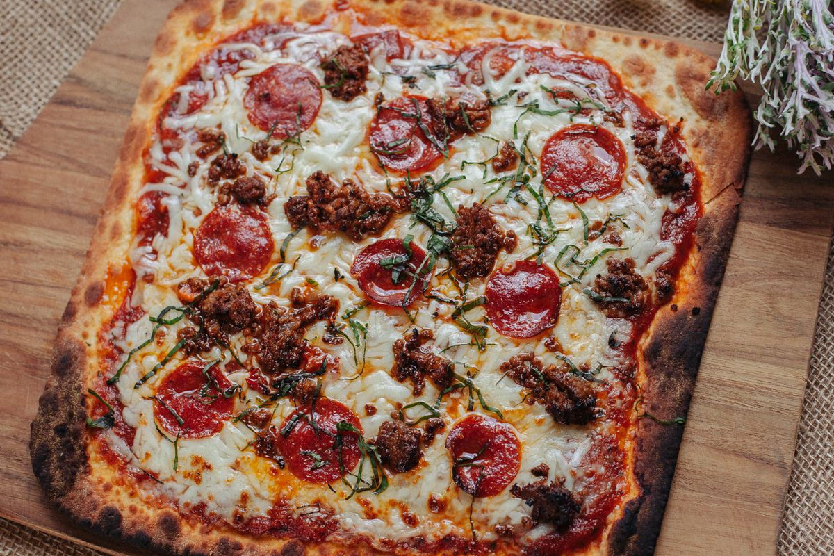 a square pizza with pepperoni and sausage on a wooden cutting board