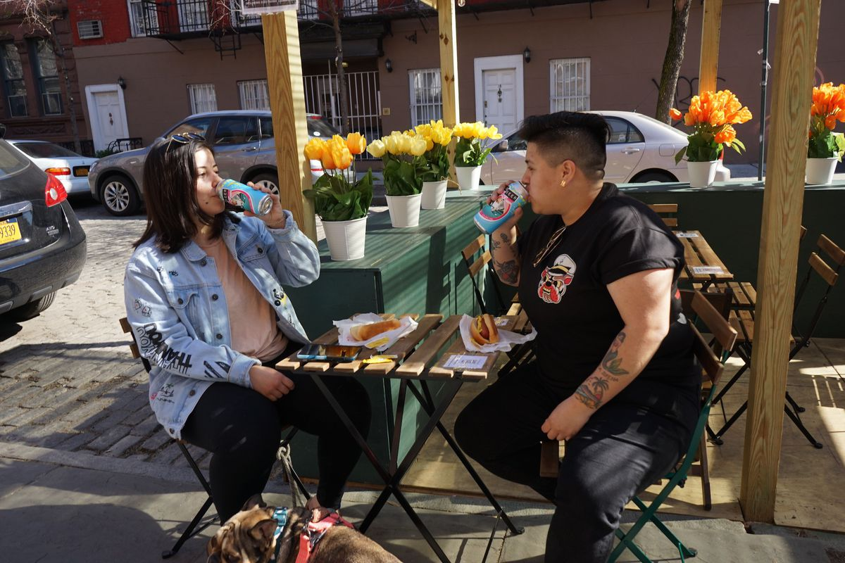 Two guests drink beer outside of Cubbyhole in the West Village