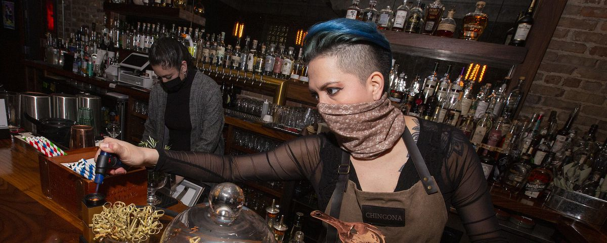 A masked bartender gets a torch out to make a drink.