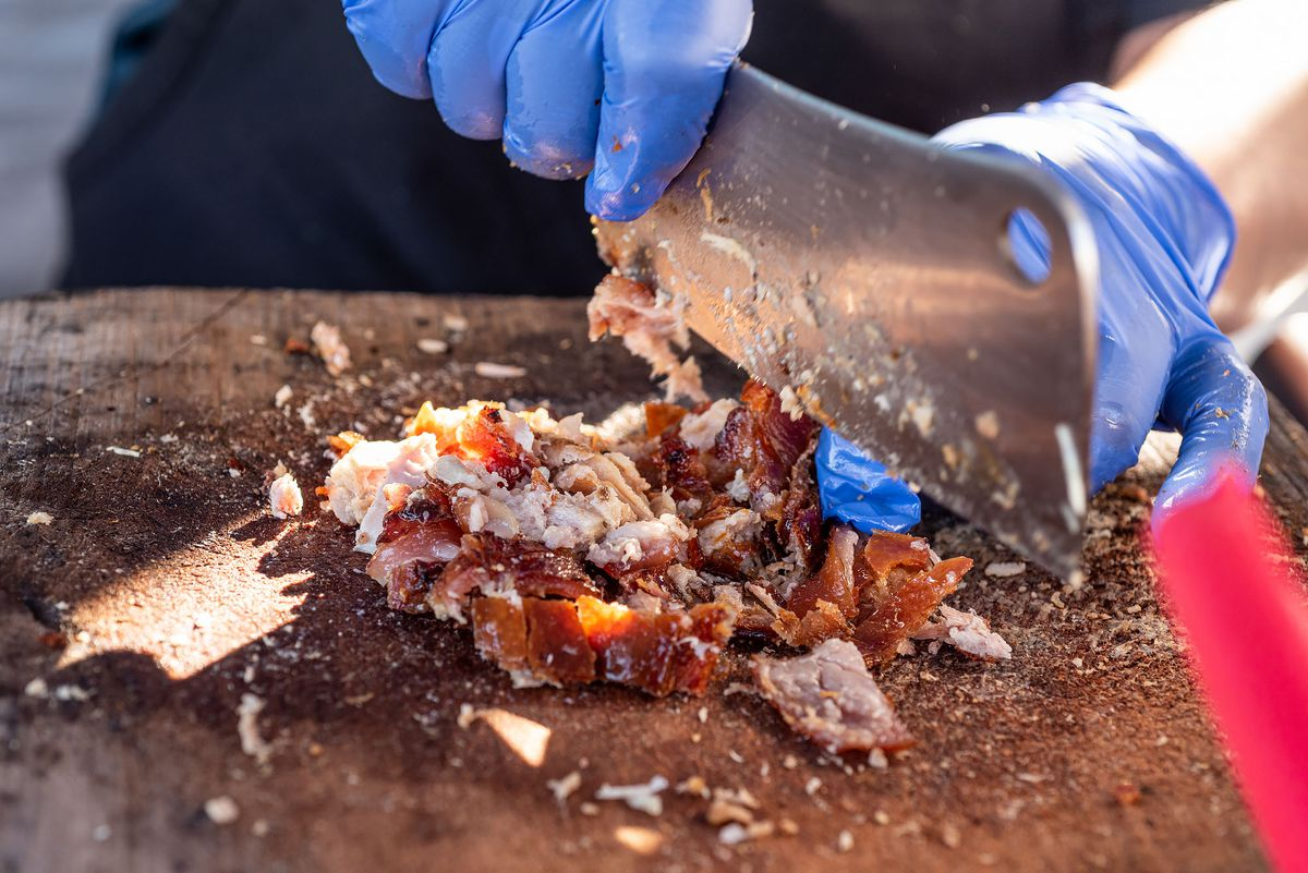 A large cleaver in blue gloved hands cutting up pork skin for tacos.