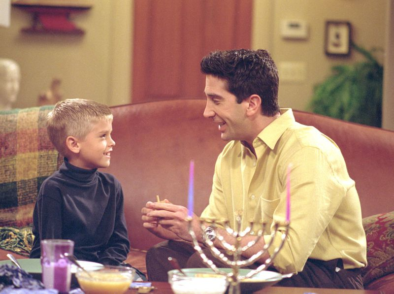Ross — free of his Holiday Armadillo garb — discusses Hanukkah with his son Ben