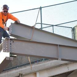 Steel worker lining up a beam in the right-center field patio -