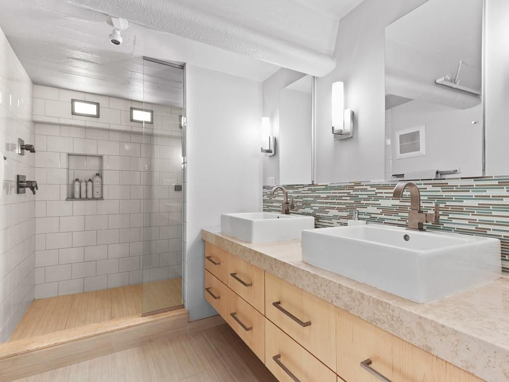 A bathroom with two basin sinks on a vanity and the vanity ends at an open shower.