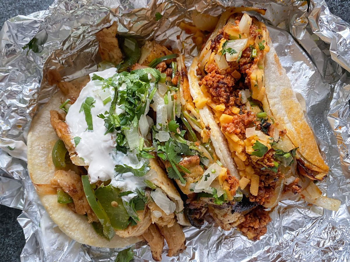 A photo of an assortment of vegan tacos from Los Gorditos, topped with vegan cheese, sour cream, and cilantro