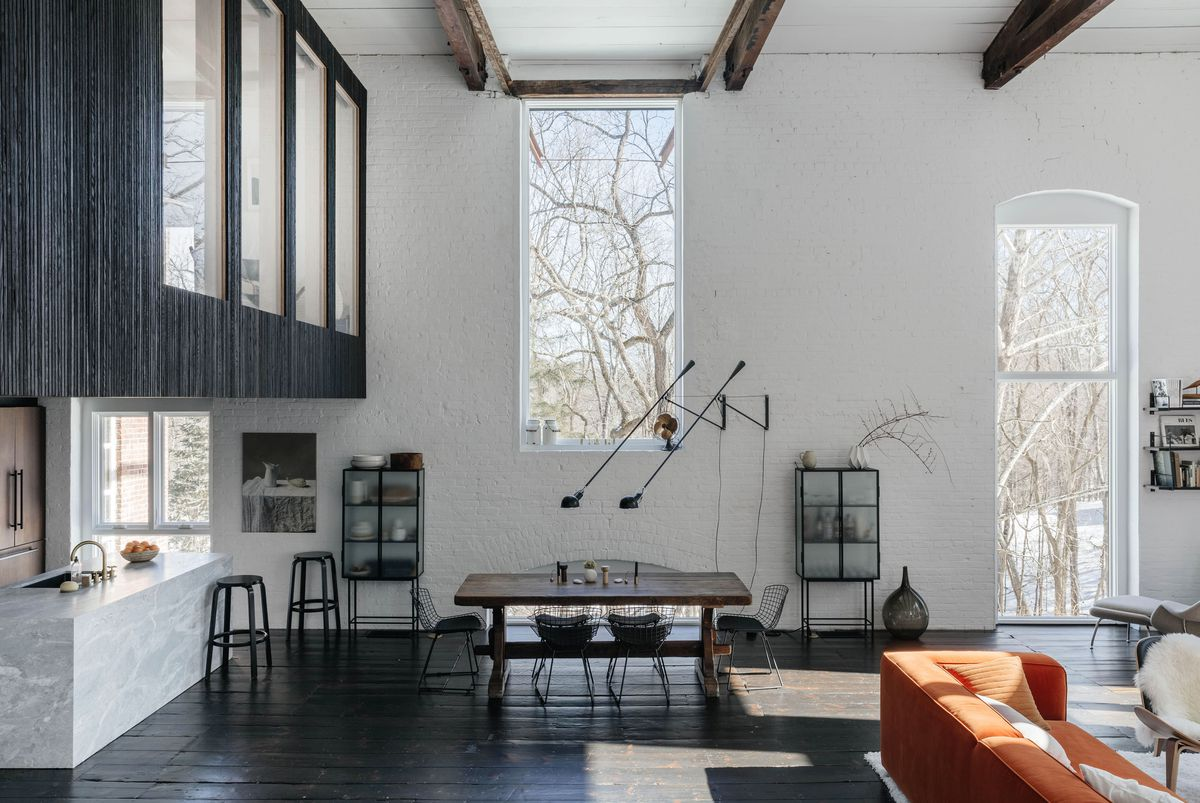Dining area with double height ceiling, large windows, wooden dining table, and marble kitchen island.