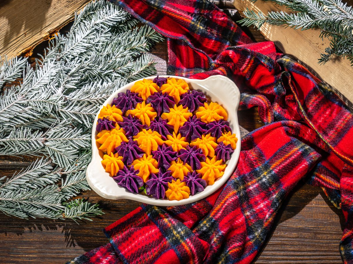 A round and white ceramic oven tin is filled with what looks to be checkered orange and purple frosting